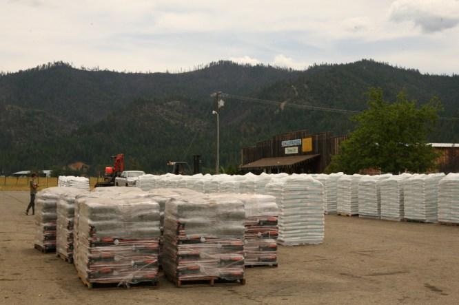 Pallets of soil outside a garden supply store.