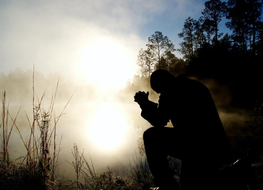 man praying at dawn