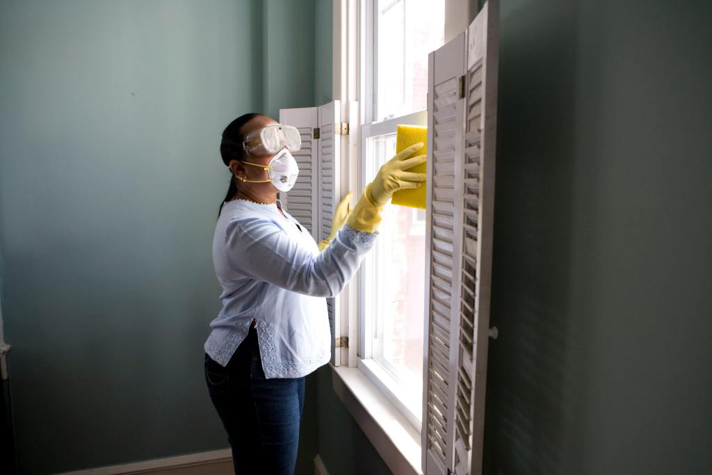 a personal washes windows with a mask and gloves