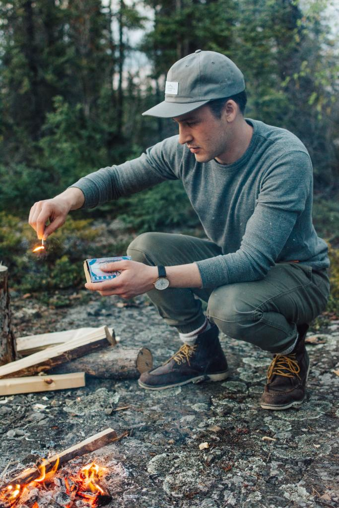 man lights campfire with matches