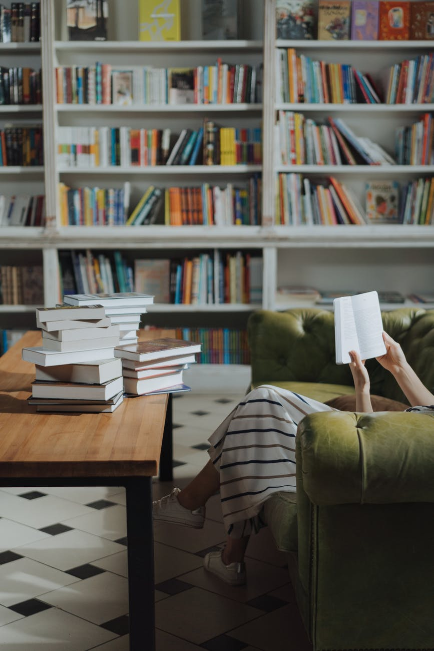 person reading book on brown wooden table