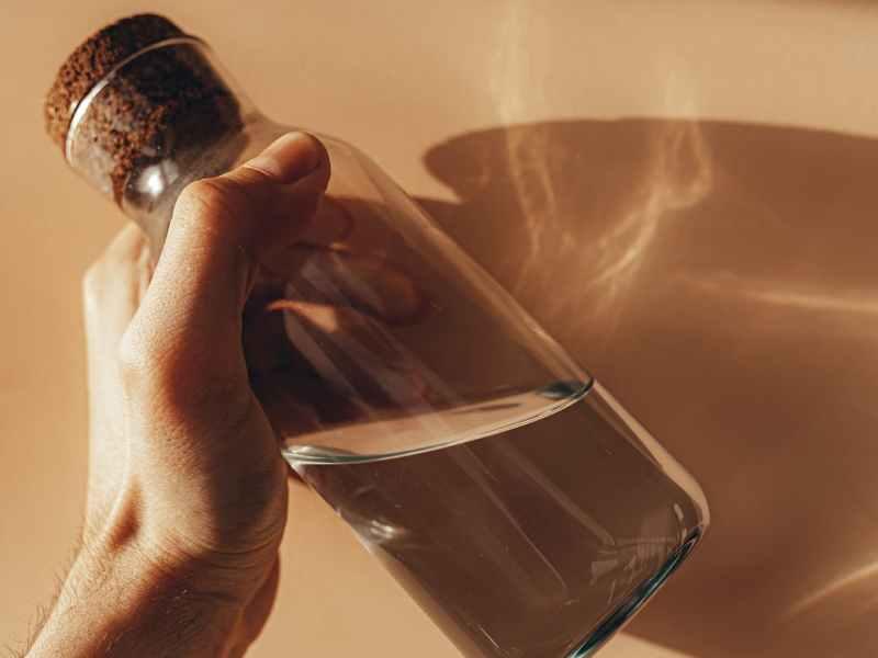 glass water bottle in hand of faceless man near wall
