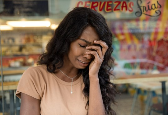 Woman crying outside a shop