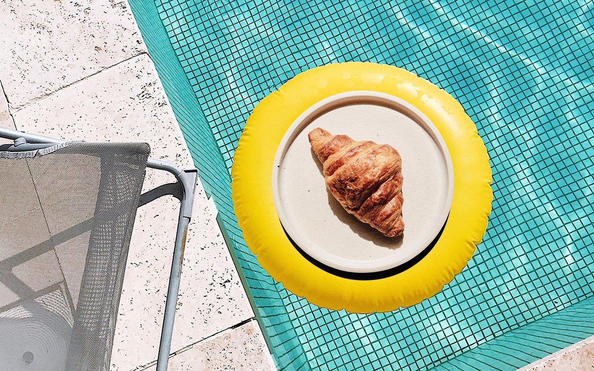 A photo of a swimming pool with a yellow inflatable ring in the middle, and a croissant superimposed over the top