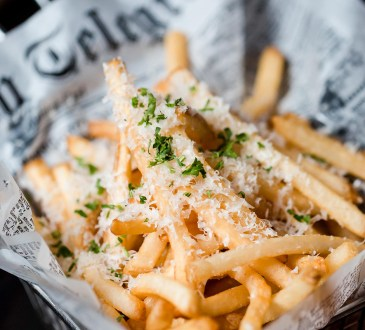 Photo of some fries topped with parmesan wrapped in newspaper