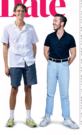 Michael and Dom – Michael is taller and wearing a white shirt and glasses and denim shorts. Dom has a beard and is in a navy shirt with pale jeans