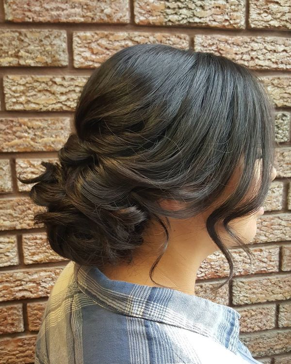 Flat Glossy Hair Is Braided In Scrolls And Gathered Into A Volumetric Node.  Front Wavy Layers Add Some Romance.