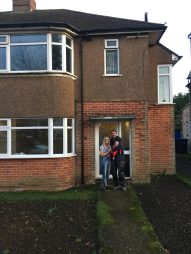 couple standing in front of house with baby