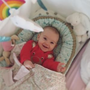baby in red babygrow smiling in green baby nest