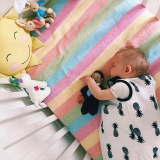 sleeping baby in black and white pineapple sleep bag on rainbow bedding