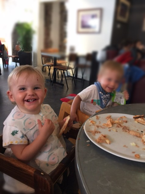 two one year olds smiling at an empty plate of pizza
