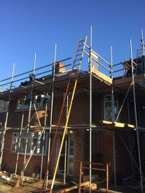 House covered in scaffolding with big orange ladder