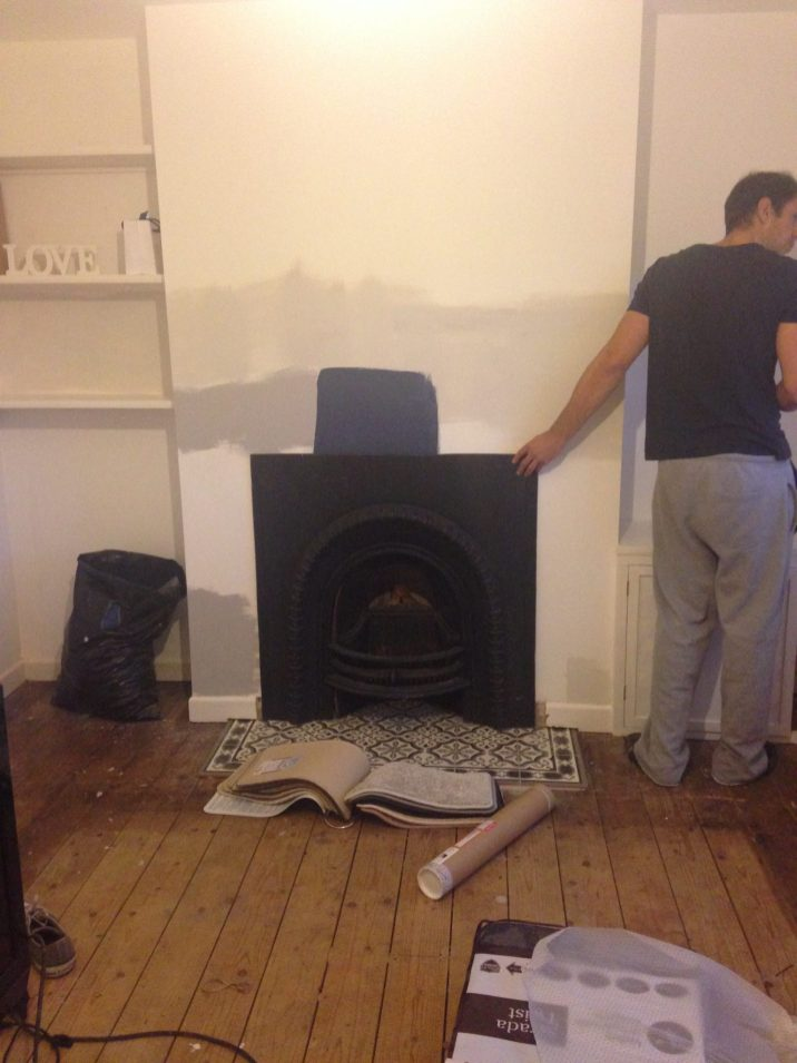 black cast iron fire place being fitted on grey and white tiled hearth. White walls with blue paint sample