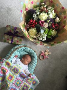 baby asleep in green baby nest with flowers
