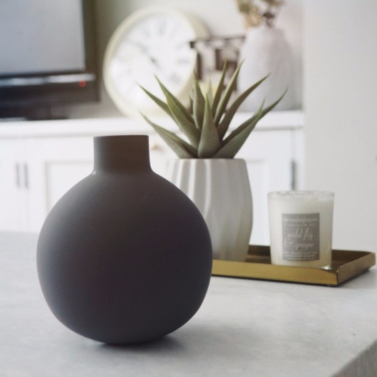 grey circular vase on table with green plant in blurred background