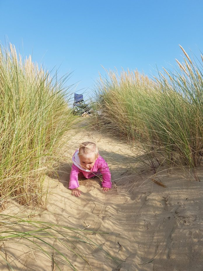 little girl in pink crawling in sand dunes | Day Trip to Camber Sands | The Halcyon Years
