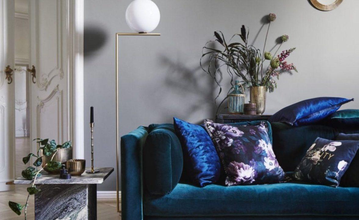 Green velvet sofa with blue velvet cushions