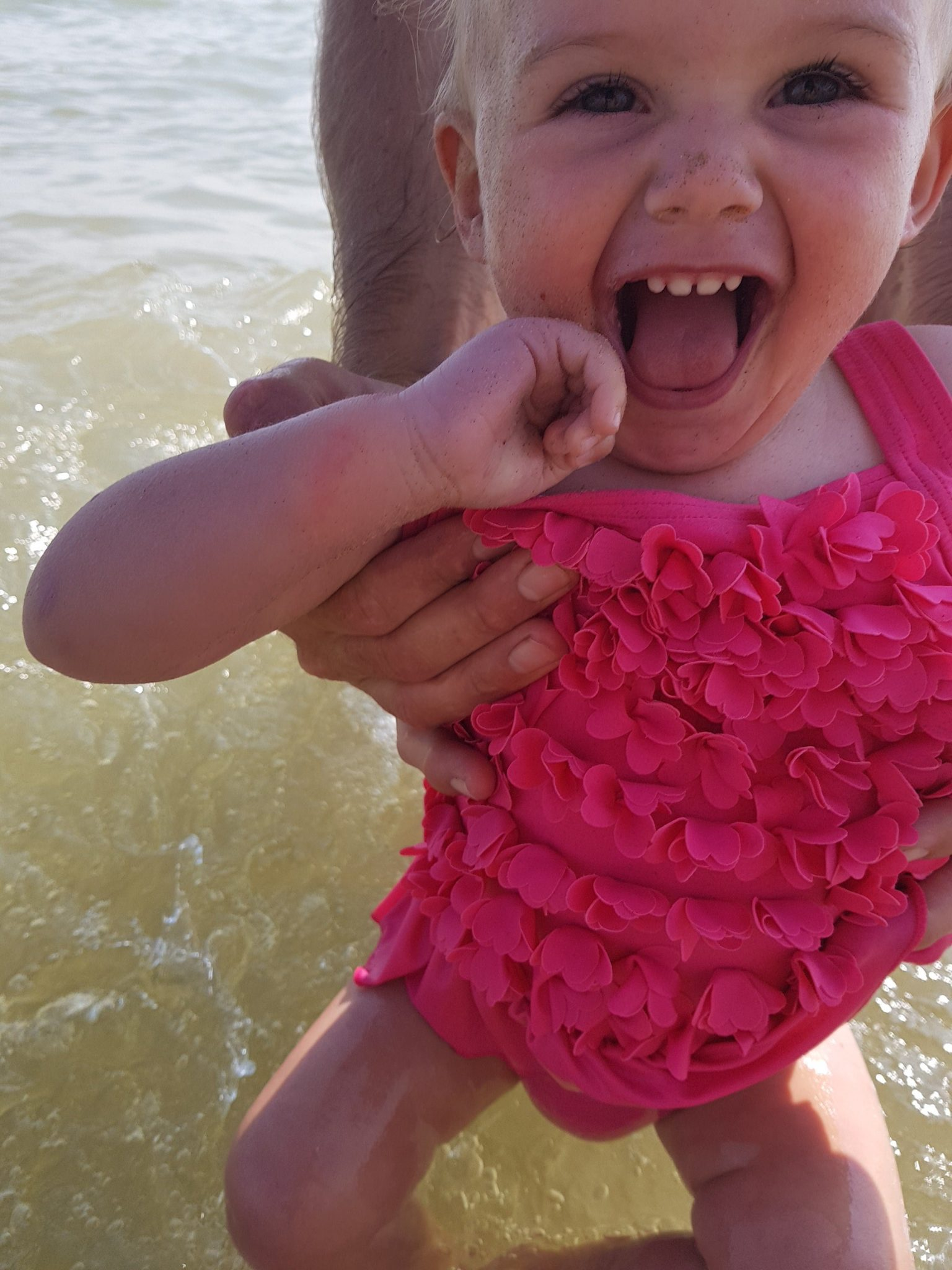 little girl smiling in sea close up