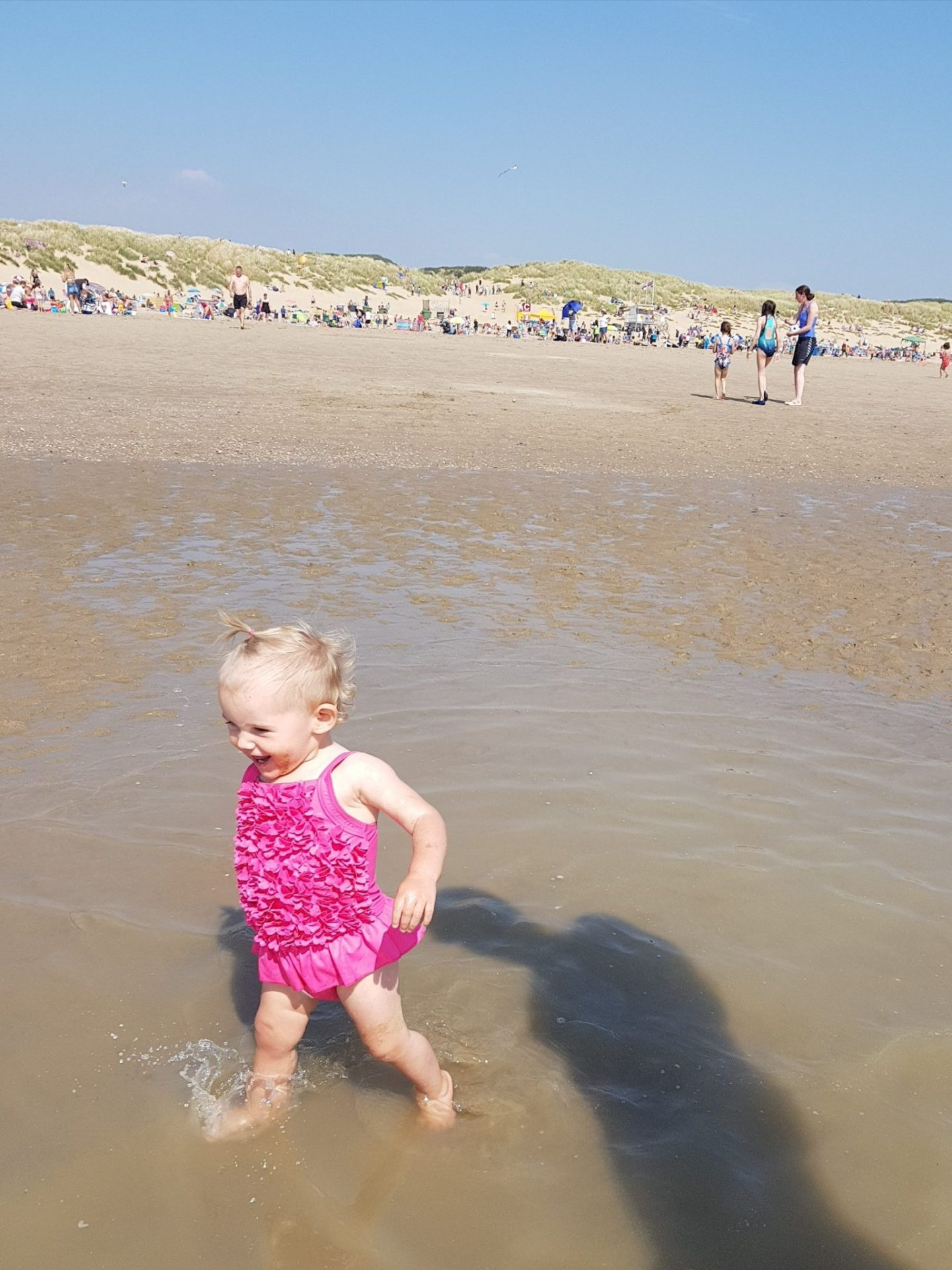 little girl running and smiling on beach