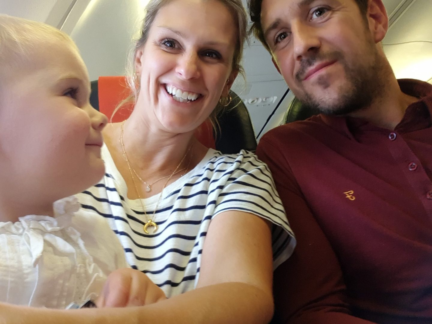 parents and daughter on aeroplane smiling