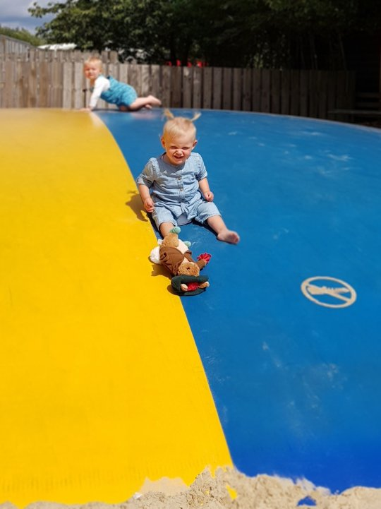 two toddlers crawling on yellow and blue big bouncy pillow