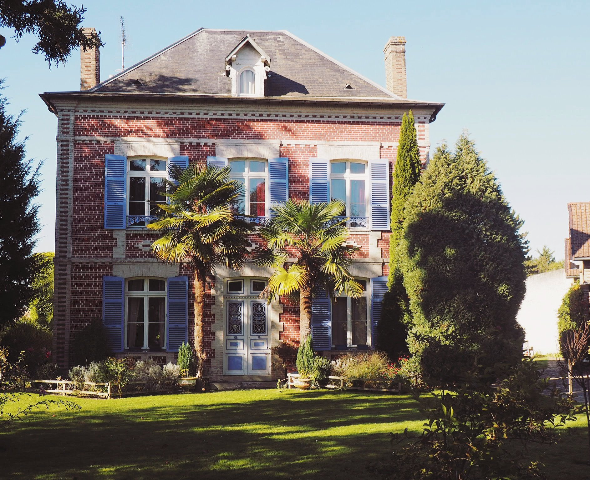 pink French house with blue shutters and blue sky
