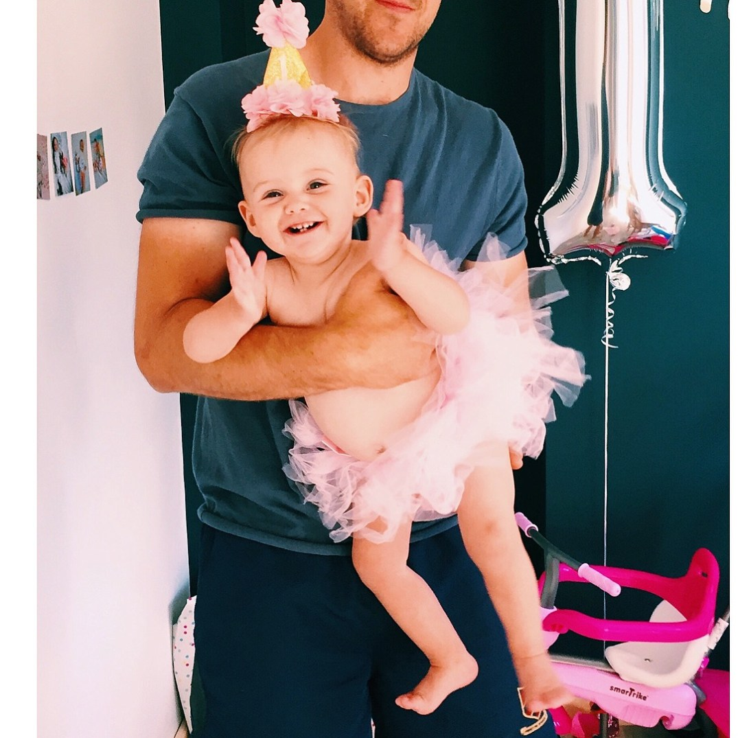 one year old girl clapping in dads arms with pink tutu on