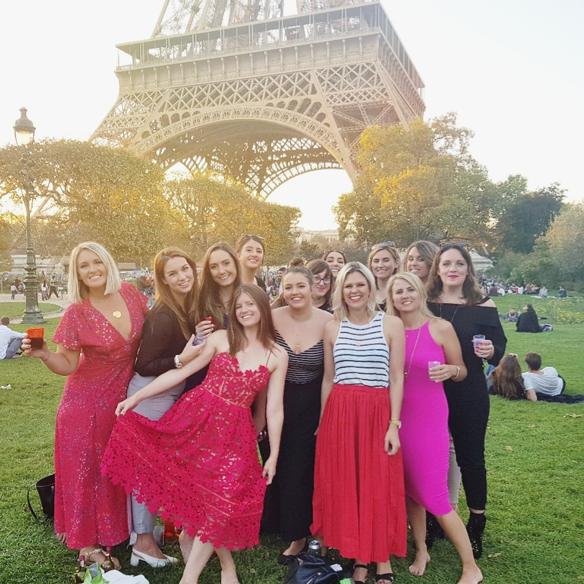 Group of girls in fabulous outfits at the eiffel tower at sunset