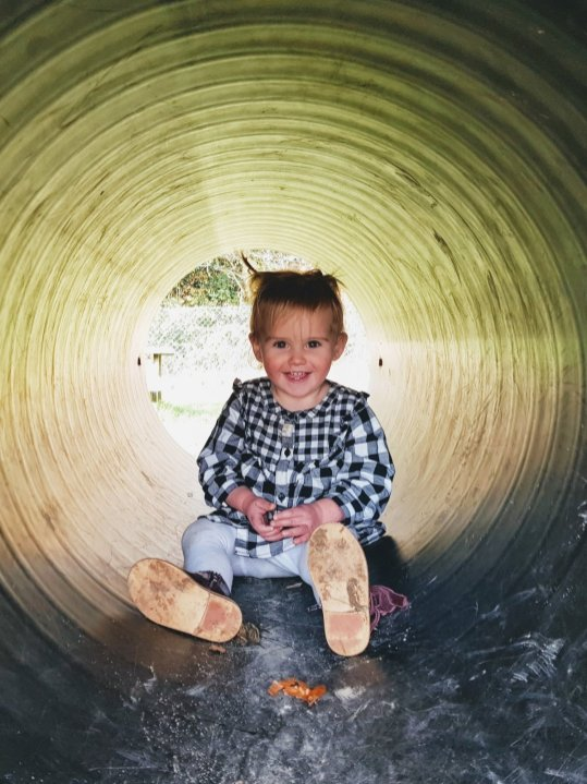 Little girl in tube at playground smiling