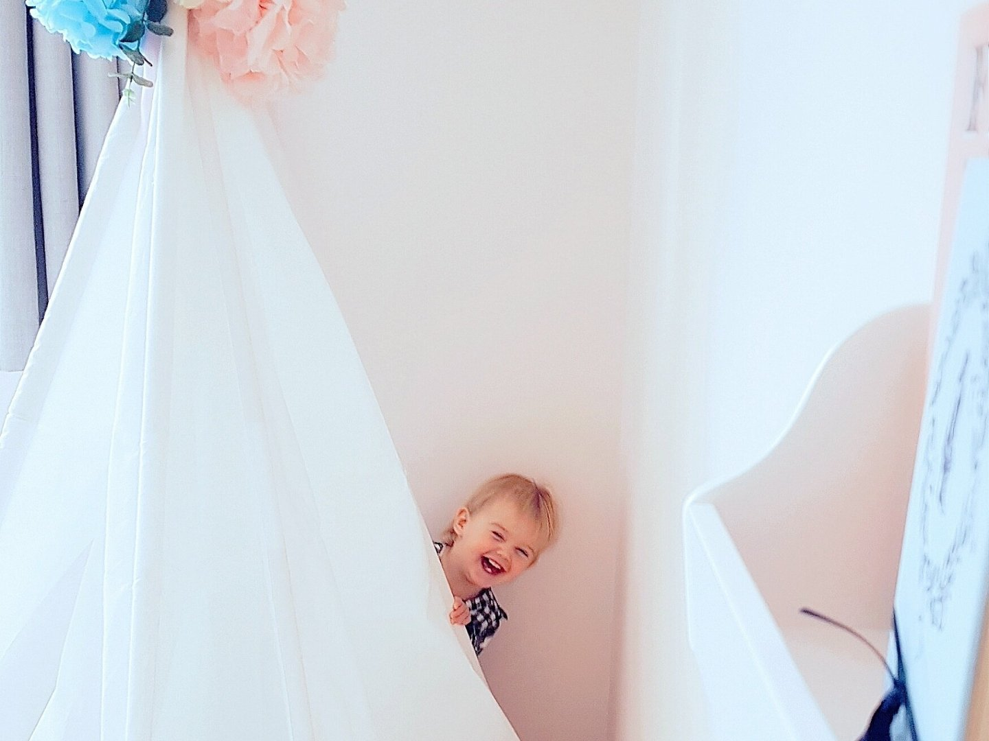 Girl in pink bedroom peeking out from behind white tipi giggling