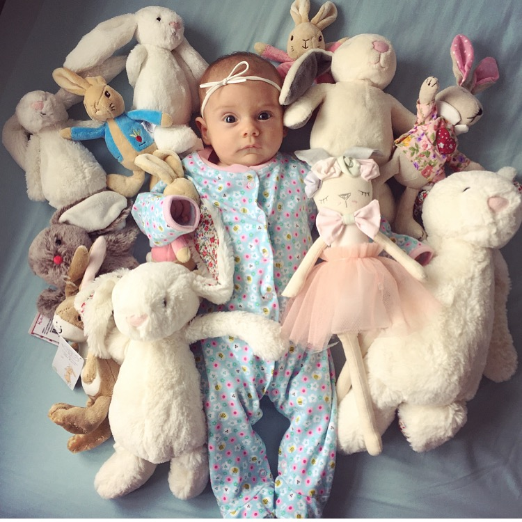Baby girl surrounded by lots of bunny teddies dainty little head bow