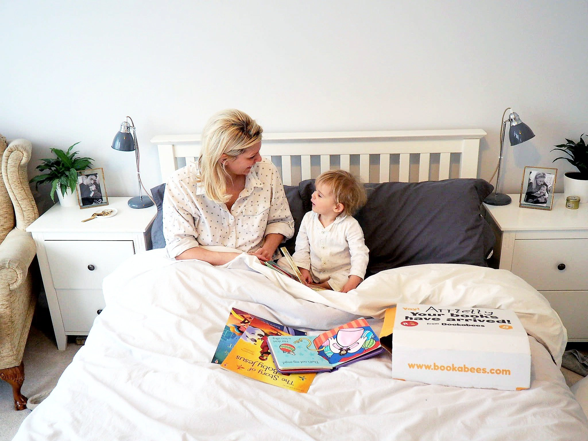 Mother and daughter reading Bookabees books in bed