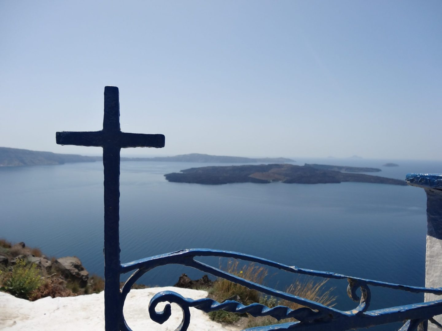 Cross in foreground of view over Caldera Babymoon complete guide to Santorini