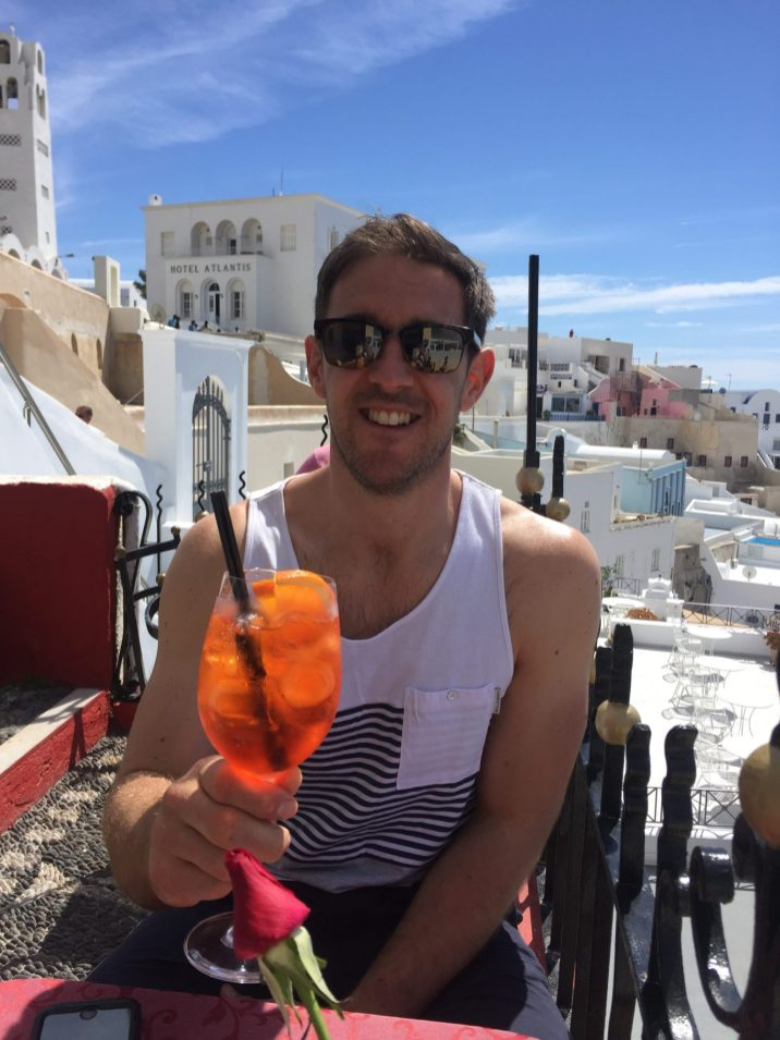 Man drinking aperol spritz Babymoon complete guide to Santorini