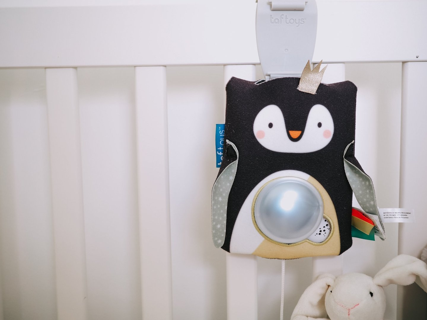 Taf Toys Prince the Penguin baby soother, review | Black penguin baby toy hung on the side of a white cot
