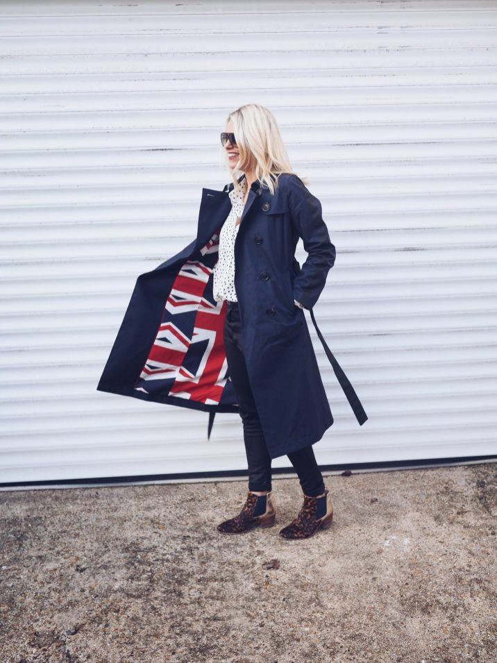 Boden staples for a capsule weekend wardrobe | The Halcyon Years [lady walking wearing navy blue trench coat with union jack lining)
