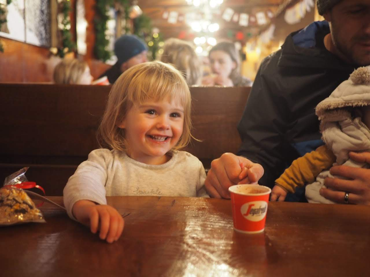 2 year old girl smiling with a mini hot chocolate at Tulleys Farm at Christmas