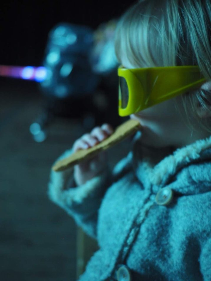 toddler girl in 3d glasses eating a cookie at Tulleys farm at Christmas