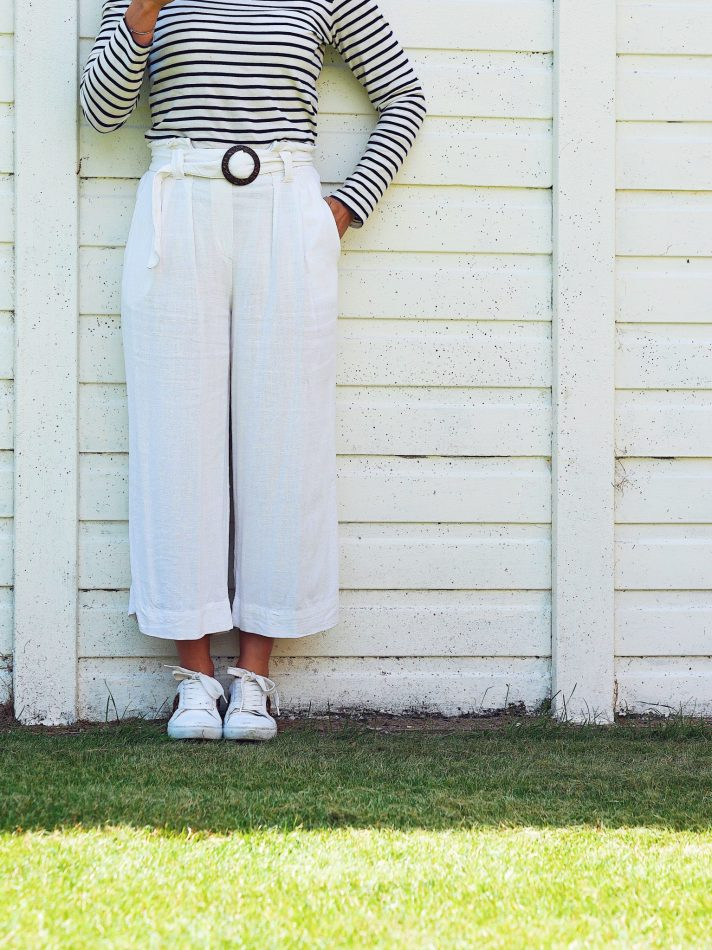 Lady in white trousers and white trainers