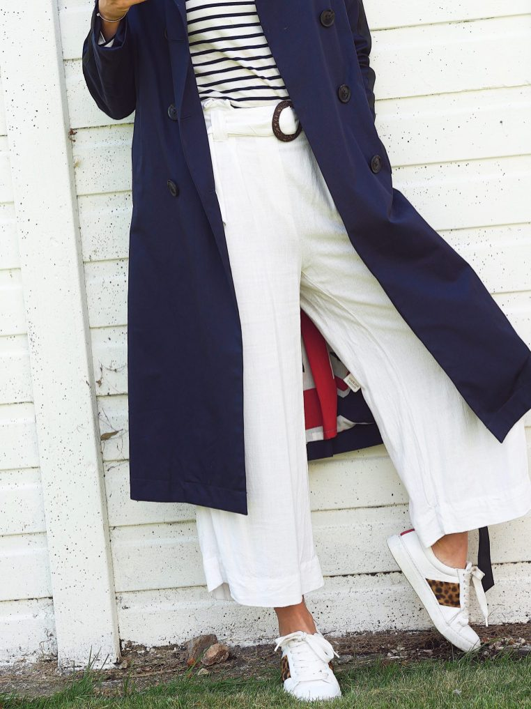 lady in white trousers, blue trench coat and white trainers