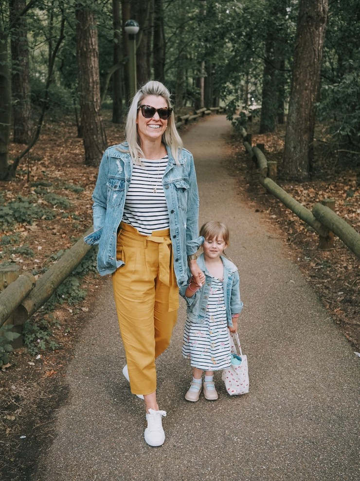 mother and daughter in matching denim jackets coloured trousers and white trainers