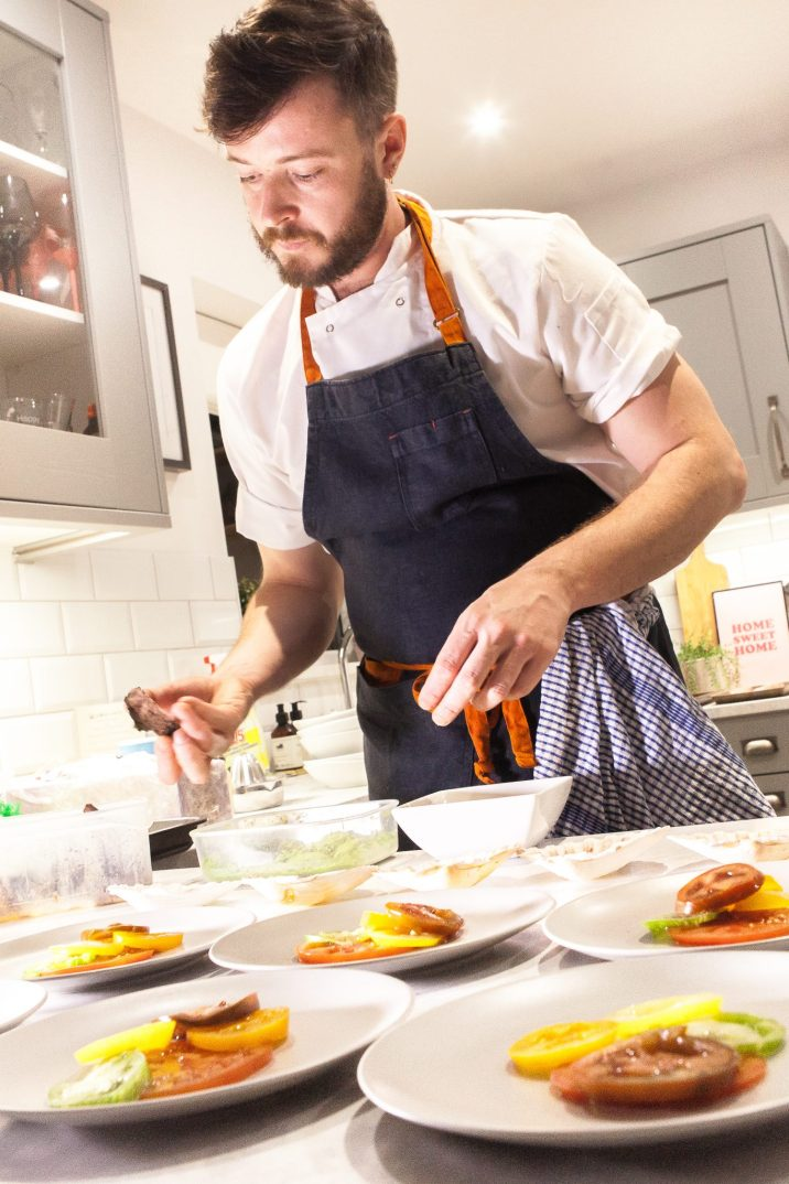 La Belle Assiette Chef putting the finishing touches to a dish in a grey kitchen