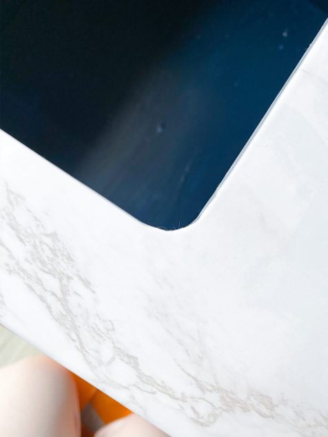 close up on marble contact vinyl around a curved hole on ikea play kitchen
