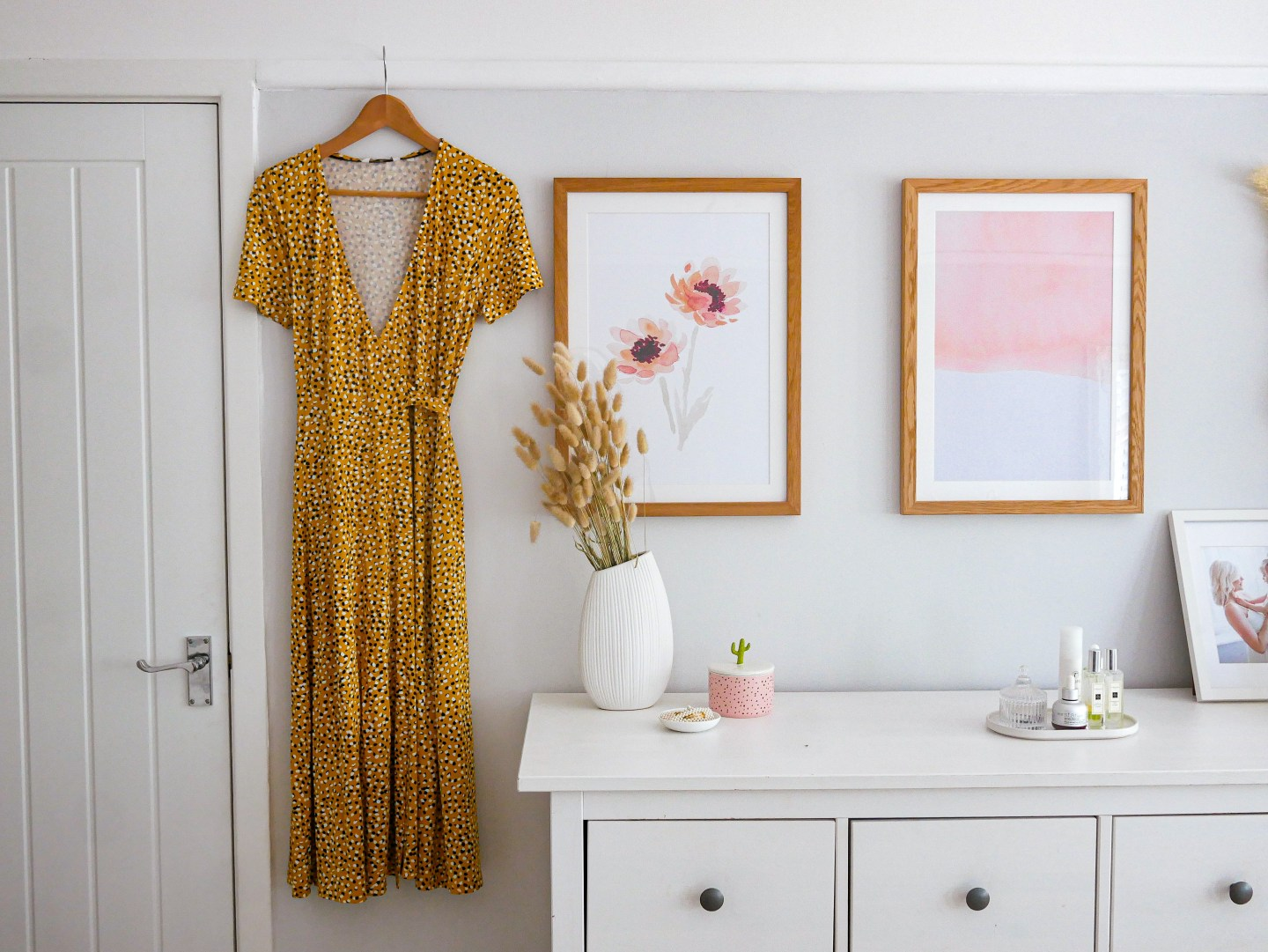 A yellow dress hanging off the picture rail in a grey bedroom next to two peach prints in wooden frames