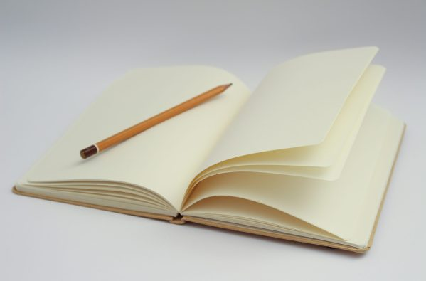 A notebook opened to a blank page with a pencil.