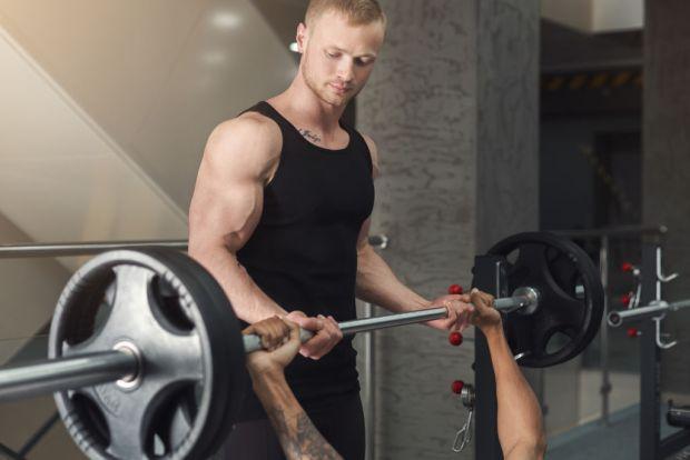 Beneficios de tener un entrenador personal - man-and-personal-trainer-exercising-with-dumbbell-p7f5smn
