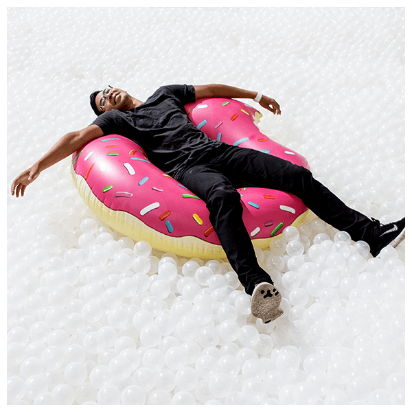 guy-sitting-in-donut-float-white-balls-chicago-January-events-thehauteseeker