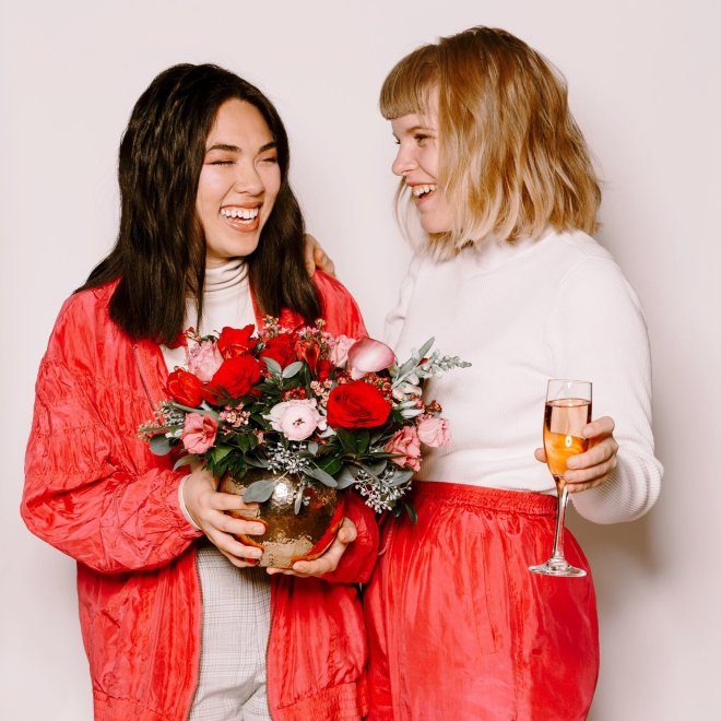 two women-one holding wine-another holding bouquet of flowers-flowers for dreams-valentines day-2019
