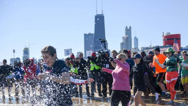 People jumping into the water during the Annual Chicago Polar Plunge featured in the March Guide of Events in Chicago 2019 on TheHauteSeeker.com