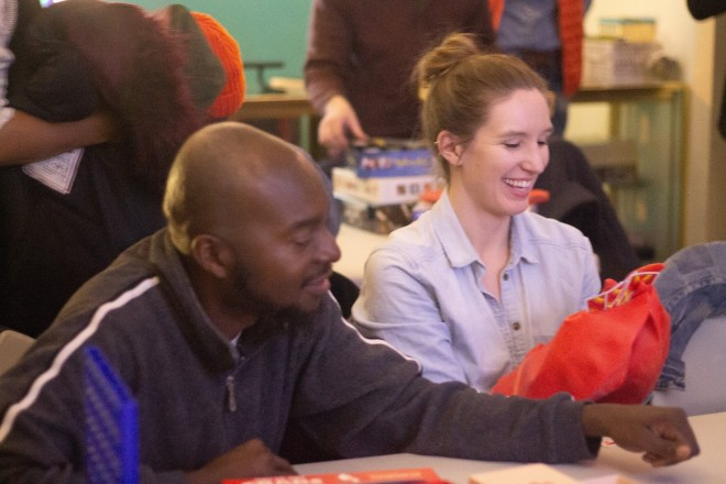 One black man and one white woman smiling and playing a game image featured on The Haute Seeker list of cool and cheap things to do on a weekday in chicago